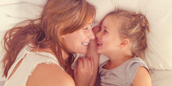 Mutter und Kind kuscheln im Bett und lachen