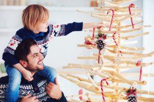 Kind schmückt mit Vater Weihnachtsbaum