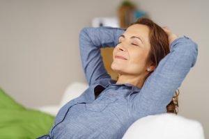 Frau sitzt auf der Couch und atmet durch