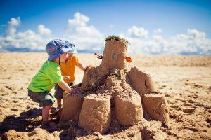 zwei Kleinkinder bauen gemeinsam eine Sandburg