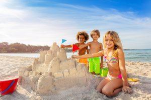 Kinder bauen gemeinsam eine Sandburg am Strand