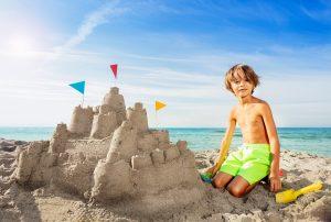 ein junge sitzt neben einer selbst gebauten sandburg