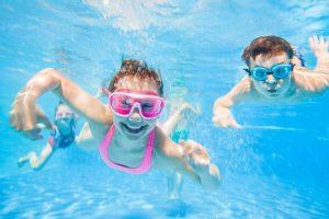 Kinder tauchen im Schwimmbecken