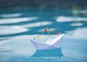 ein papierschiff schwimmt im wasser