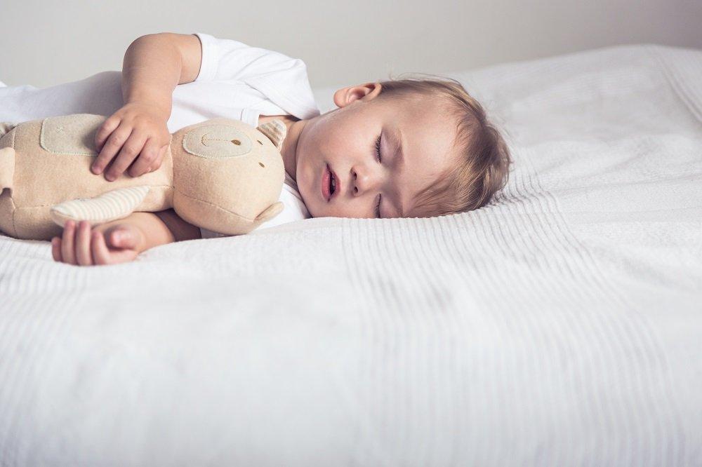 Kind schläft mit Stofftier