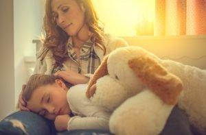Kind schläft im Arm der Mutter