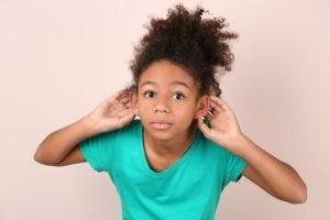 Kind hält sich die Hände an die Ohren