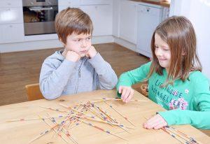 Kinder beim Mikado spielen