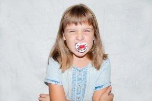 aggressives Mädchen mit Schnuller im Mund