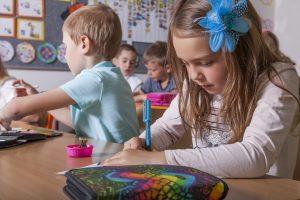 ein maedchen sitzt in der klasse und schreibt