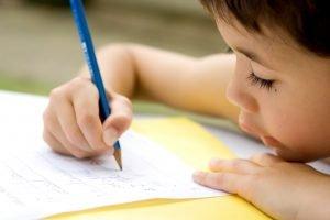 Kind schreibt auf Papier