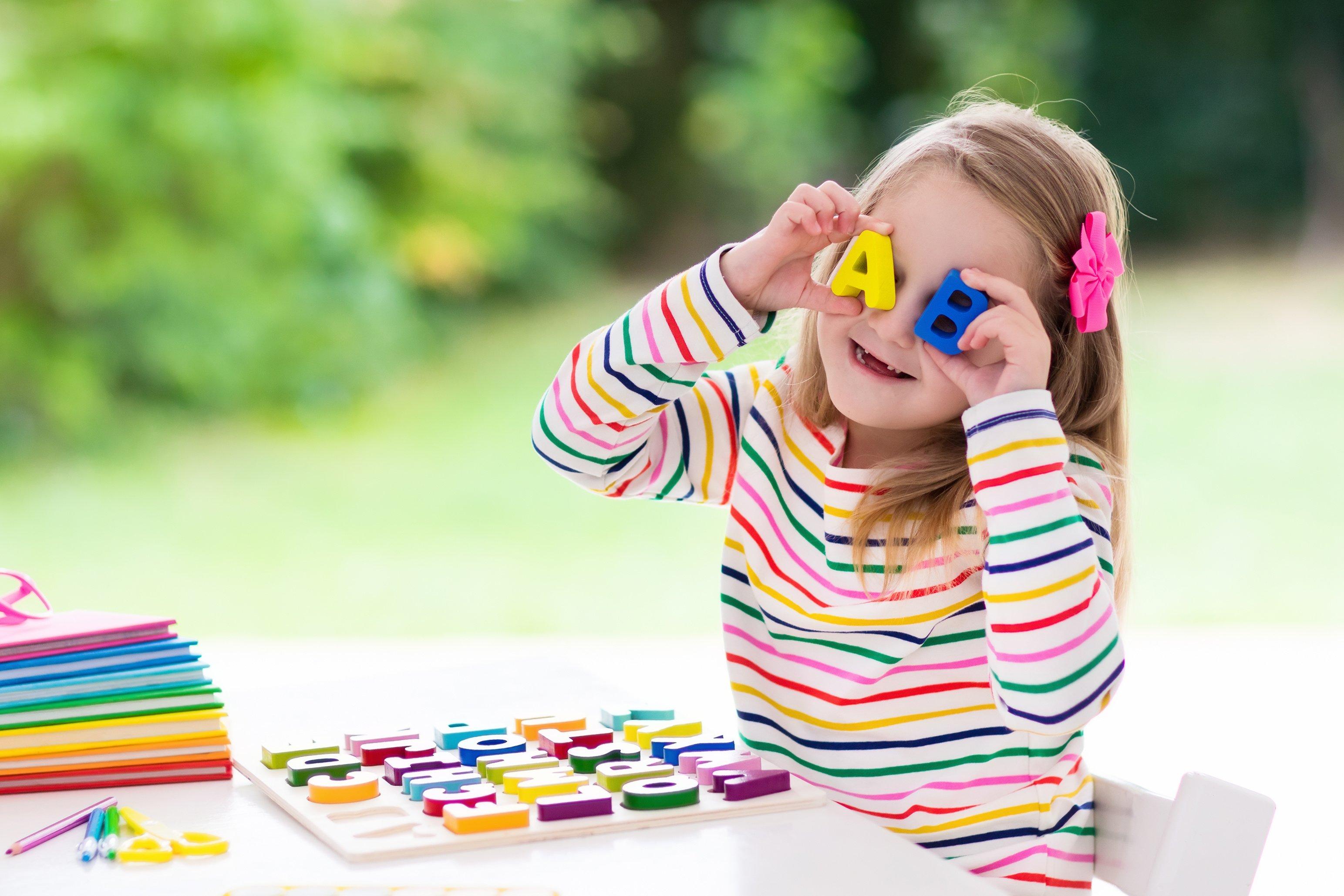 Kind hält sich Spielzeug Buchstaben vor die augen