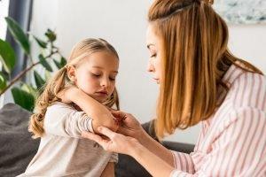 Mutter versorgt die Schürfwunde ihrer kleinen Tochter