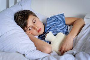 Kind liegt traurig mit Bauchschmerzen im Bett
