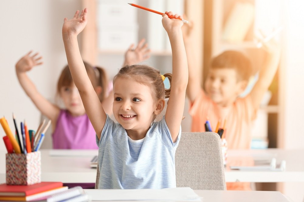 kinder heben arme im unterricht