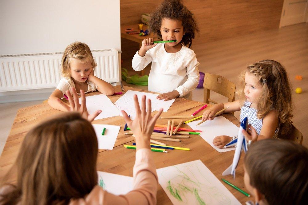 Kinder basteln mit Erzieherin am Tisch
