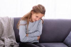 maedchen sitzt mit bauchschmerzen auf der couch