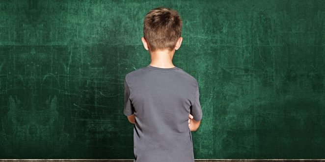kind steht bockig vor einer tafel