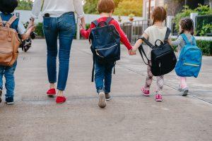 mutter mit kindern auf dem schulweg