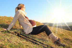 schwangere frau ruht sich waehrend des wanders aus