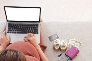 schwangere Frau sitzt auch Couch am Laptop