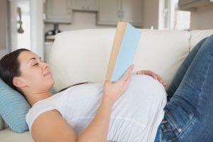eine schwangere frau liegt mit einem buch in der hand auf dem sofa