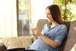 eine schwangere frau mit einem smartphone in der hand