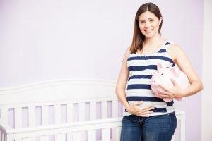 schwangere frau haelt ein sparschwein in der hand