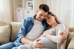 Mann streichelt den Bauch seiner schwangeren Frau