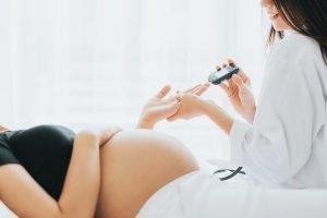 schwangere frau bekommt von ihrer aerztin den blutzucker gemessen
