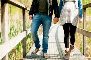 werdende eltern gehen hand in hand spazieren