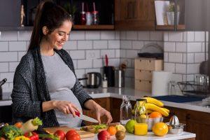 Schwangere Frau bereitet gesundes Essen zu