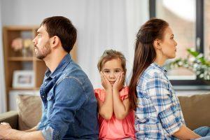 ein Kind sitzt zwischen Vater und Mutter, die sich nicht ansehen