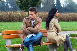 ein junges Paar sitzt auf einer Parkbank und streitet