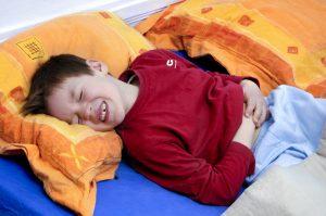 Kinder liegt mit schweren Bauchkrämpfen im Bett
