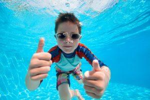 junge schwimmt unter wasser und haelt die daumen hoch