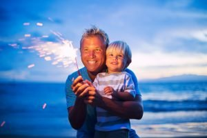 Vater und Sohn zünden eine Wunderkerze an