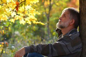 ein Mann sitzt an einem Baum
