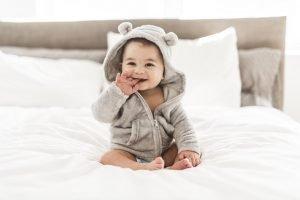 ein Baby sitzt auf einem Bett