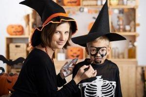 Mutter schminkt ihren Sohn für Halloween als Skelett