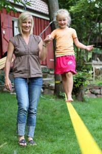 Mutter hilft Kind auf einer Slackline zu balancieren