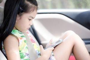Kind spielt bei Autofahrt an Handy