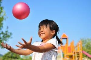 Kind möchte einen Softball fangen