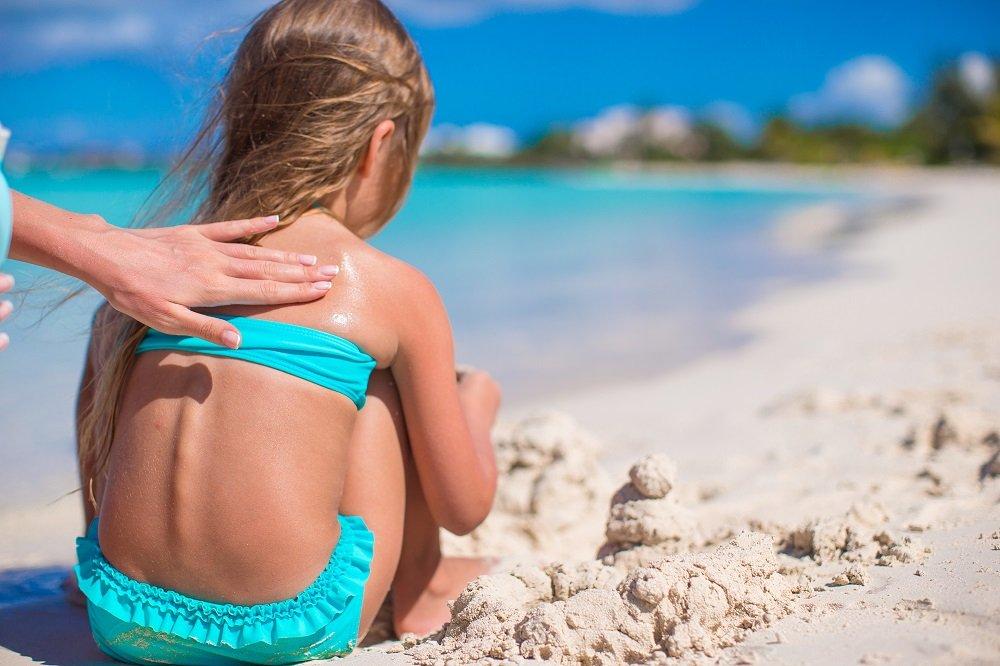 Kind wird an Strand eingecremt.