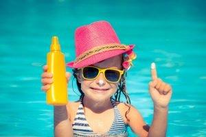 Kind mit Sonnenschutz im Wasser