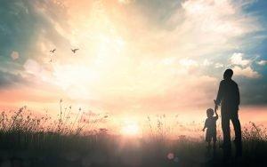 Vater sieht sich mit seinem Kind einen Sonnenuntergang an