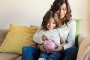 Mutter wirft zusammen mit ihrer Tochter Geld in ein Sparschwein