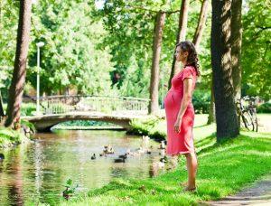 junge, schwangere Frau in einem Park