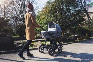 mutter geht mit dem kinderwagen spazieren