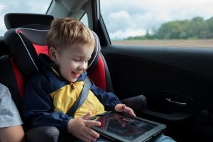 Kind spielt im Auto am Tablet
